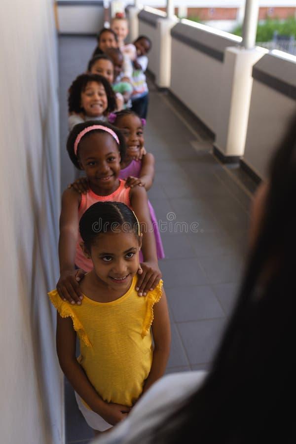 有站立在行的老师的Schoolkids用他们的在肩膀的手在走廊 免版税图库摄影