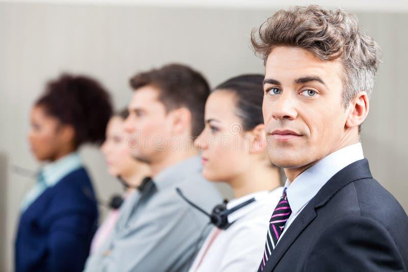 有站立在行的雇员的确信的经理 免版税库存图片