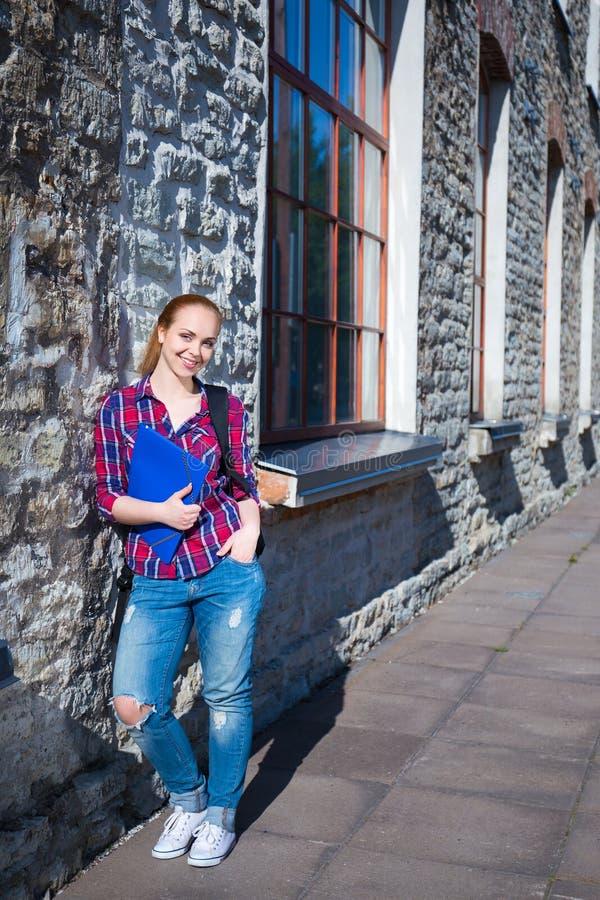 有站立在街道上的背包的微笑的少年学生女孩 免版税库存照片