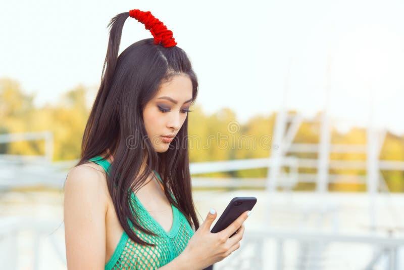 有站立在街道的智能手机的愉快的年轻亚裔妇女 免版税库存图片