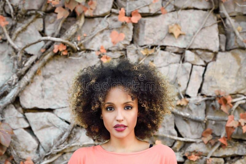 有站立在都市公园的非洲的发型的黑人妇女 免版税库存图片