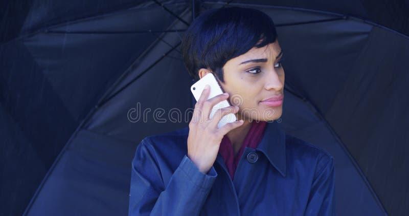 有站立在雨中的伞的非裔美国人的妇女使用手机 免版税库存照片