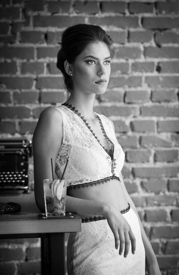 有站立在餐馆桌附近的白色礼服的时兴的可爱的夫人喝一杯 深色的头发短小妇女 免版税库存照片