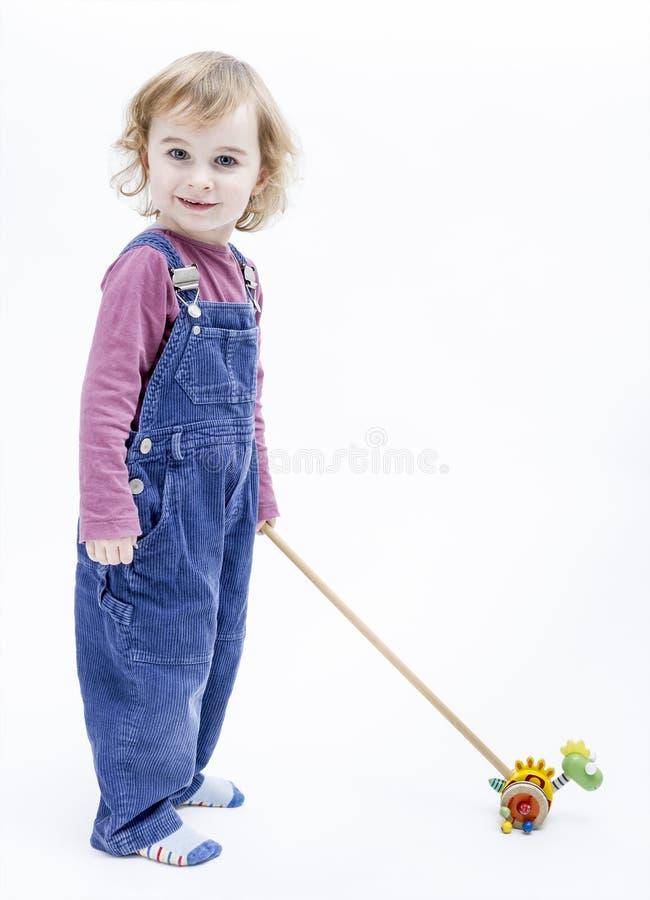 有站立在轻的背景中的玩具的学龄前儿童 库存照片