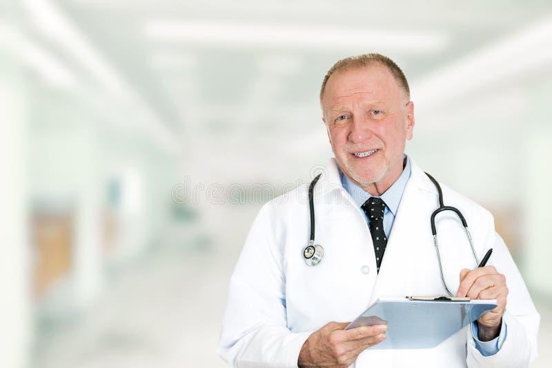 有站立在医院走廊的剪贴板的愉快的资深医生 库存图片