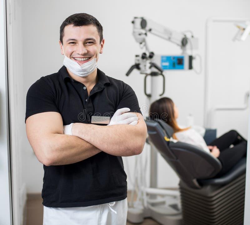 有站立用他的手的陶瓷托架的友好的男性牙医横渡了在牙齿诊所 口腔医学 免版税图库摄影