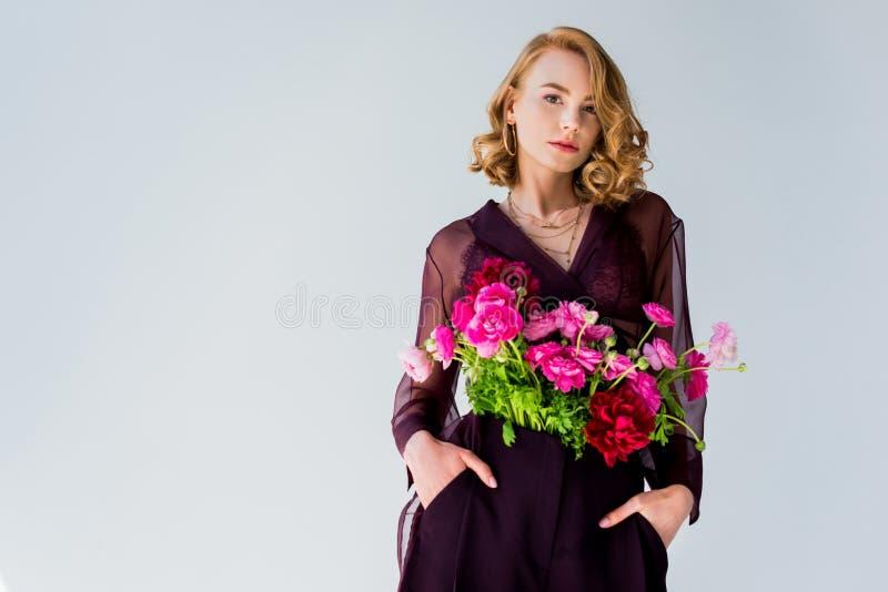 有站立用在口袋的手和看照相机的嫩桃红色花的美丽的年轻女人 免版税图库摄影