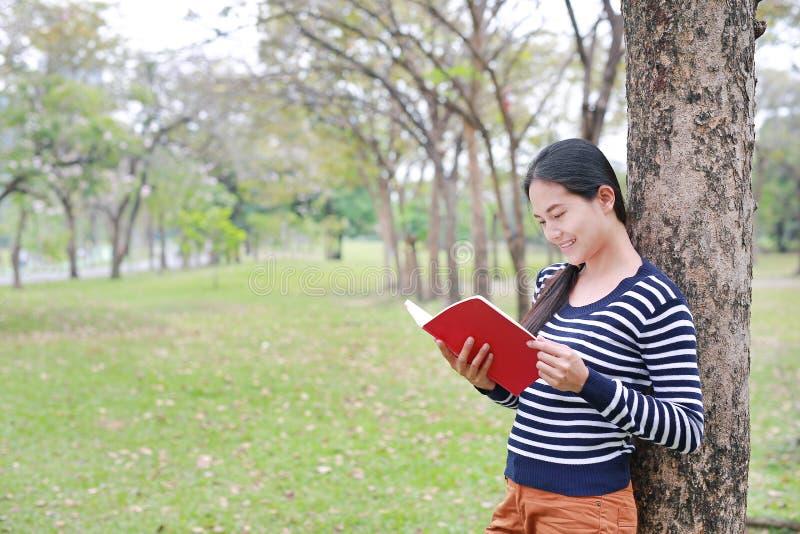 有站立的书的画象年轻亚裔妇女精瘦反对树干在室外的公园 库存照片