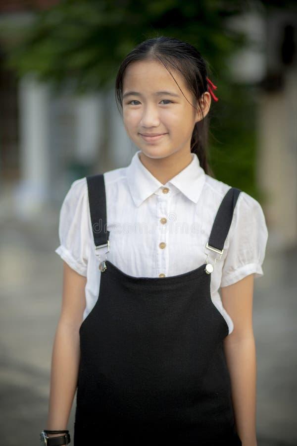 有站立的笑容的亚裔少年室外 免版税库存照片
