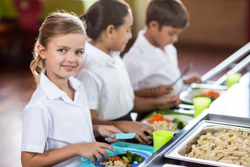 有站立近的军用餐具柜台的同学的女小学生 免版税库存图片