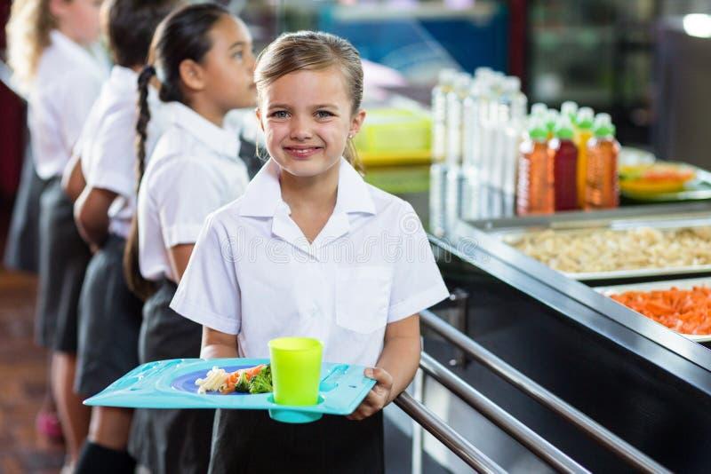 有站立近的军用餐具柜台的同学的逗人喜爱的女小学生 免版税库存图片