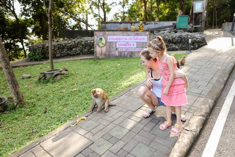 有站立近的猴子的女儿的年轻白肤金发的母亲在动物园在泰国 免版税库存照片