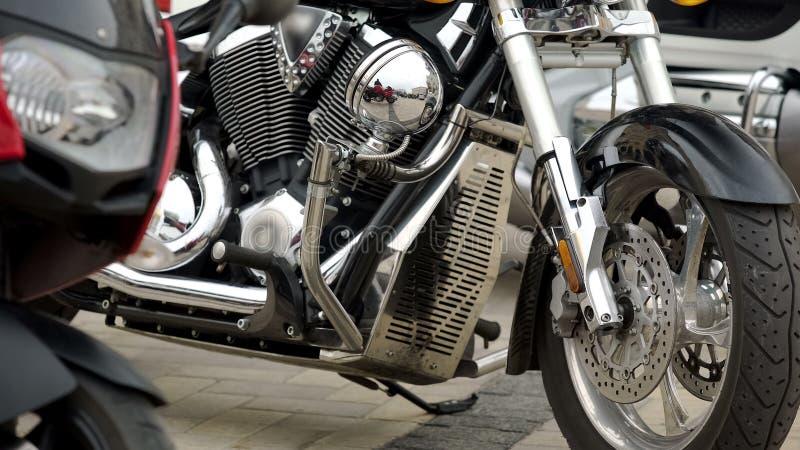 有站立防护的挡风玻璃的发光的银色摩托车户外,力量 免版税库存照片