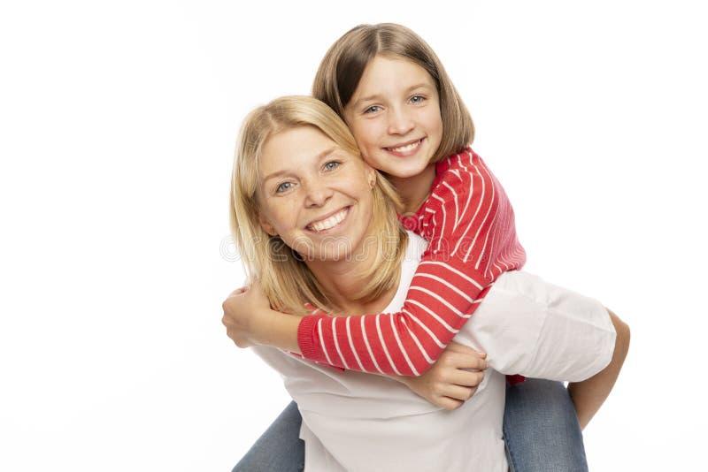 有笑她的十几岁的女儿的妈妈拥抱和 库存图片