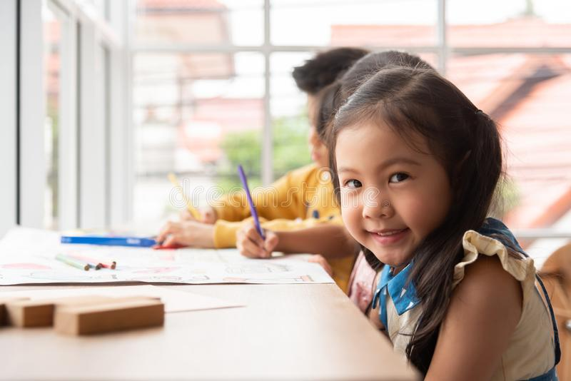 有笑容的亚裔女孩在一间教室在学校 库存图片