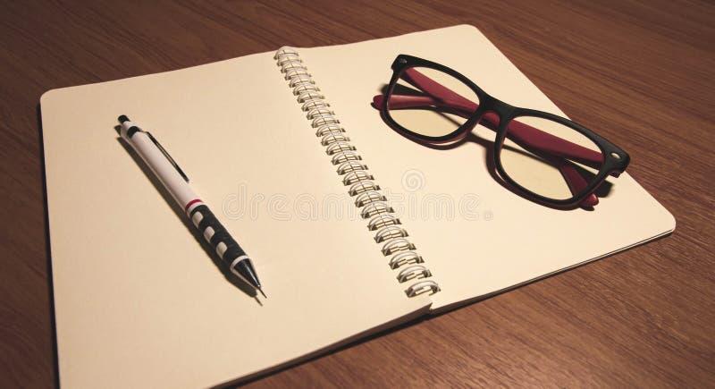 有笔和玻璃的笔记本 库存图片