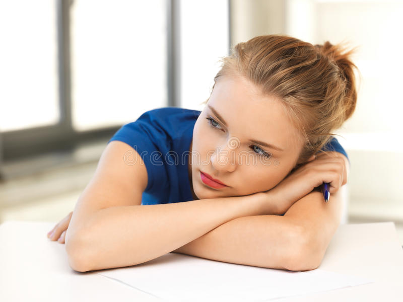 有笔和纸的疲乏的十几岁的女孩 免版税图库摄影