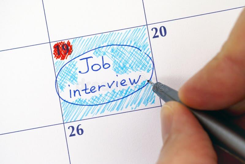 有笔文字提示工作面试的手在日历 免版税库存图片