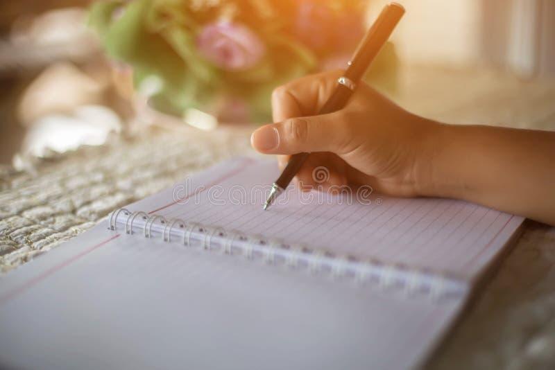 有笔文字的女性手在笔记本咖啡咖啡馆 免版税库存照片