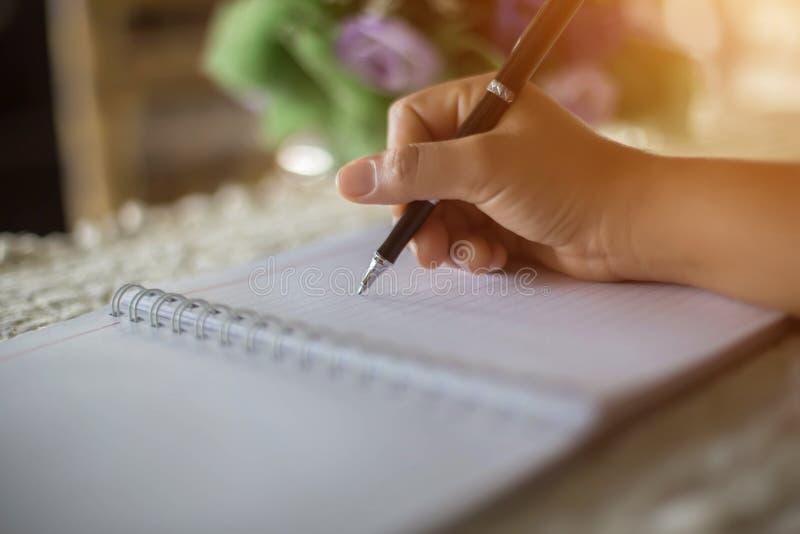 有笔文字的女性手在笔记本咖啡咖啡馆 免版税库存图片