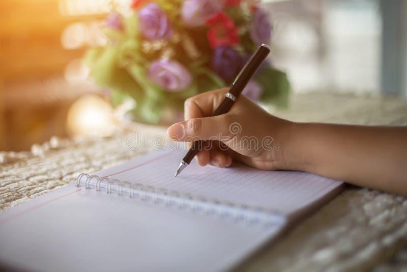 有笔文字的女性手在笔记本咖啡咖啡馆 库存图片