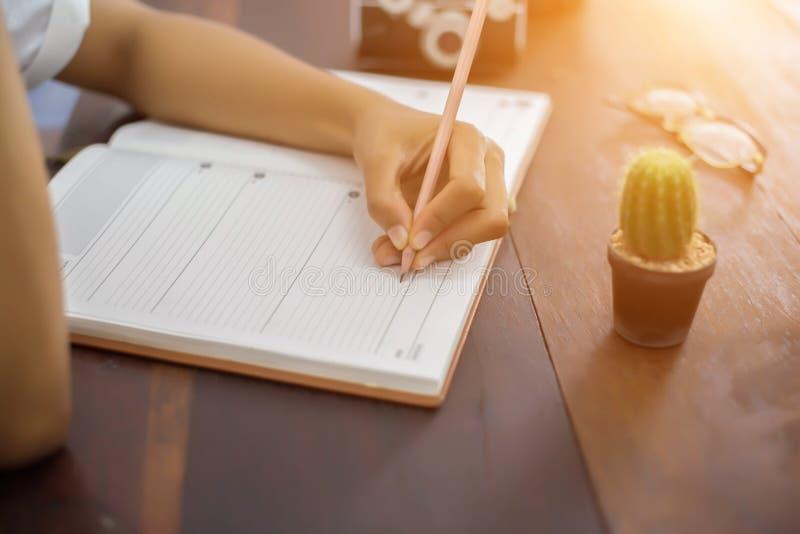 有笔文字的女性手在笔记本咖啡咖啡馆 图库摄影