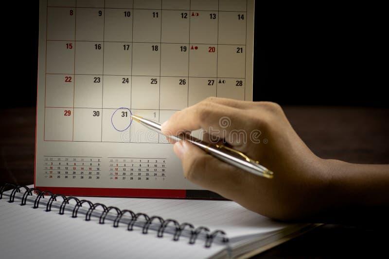 有笔文字的手在日历 免版税库存照片