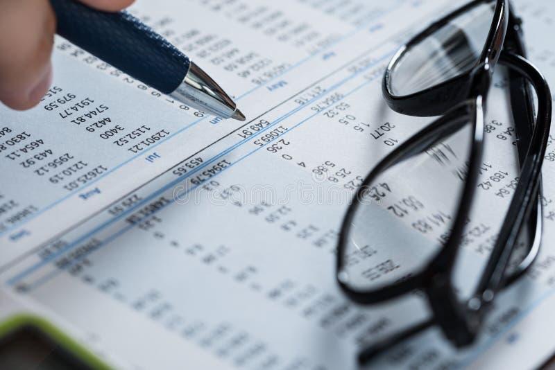 有笔的人在财政纸的手和玻璃 免版税图库摄影