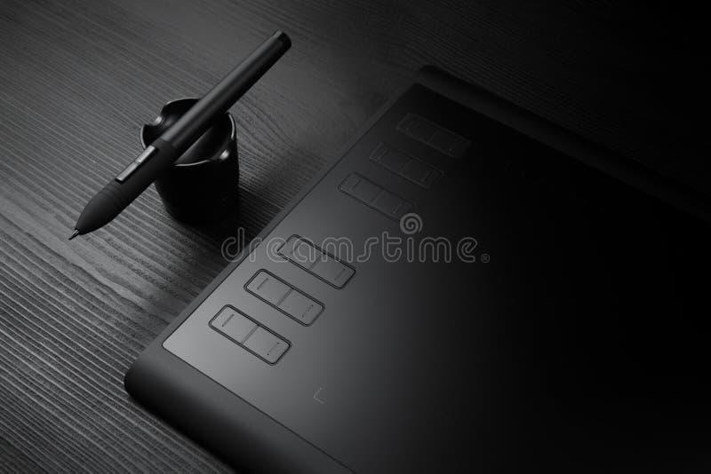 有笔的图形输入板以图例解释者和设计师的黑木背景的 库存照片