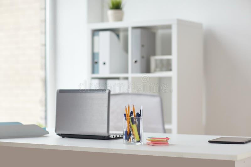 有笔的在办公室桌上的膝上型计算机和贴纸 库存图片
