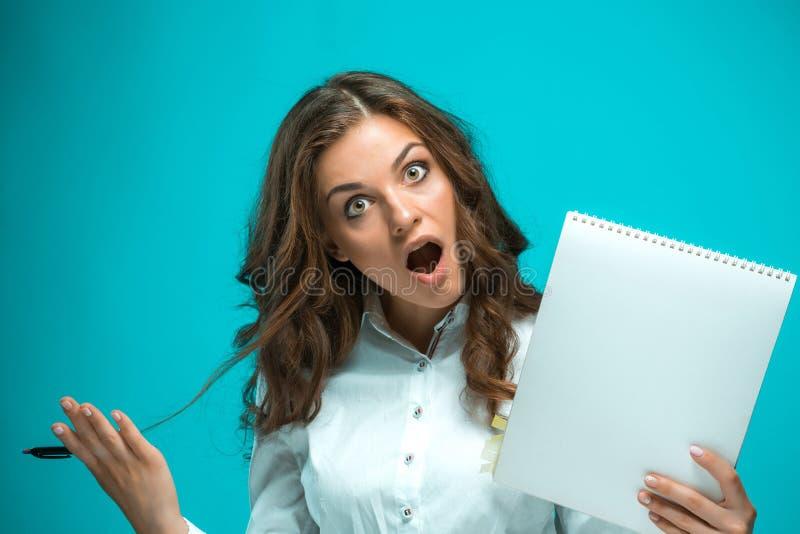 有笔的惊奇的年轻笔记的女商人和片剂关于蓝色背景 免版税库存照片
