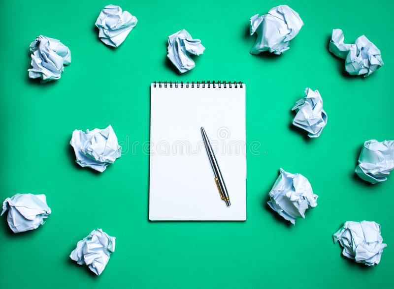 有笔的白色笔记本在纸球中的绿色背景 引起想法的概念,发明新的想法 纸球 库存图片