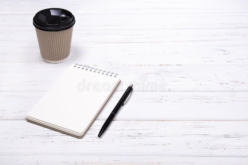 有笔的笔记本和包装纸去的工艺咖啡在与拷贝空间的白色木桌上 库存照片