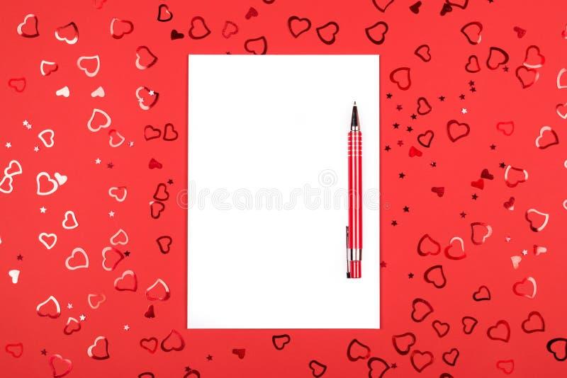 有笔的笔记本在与心形的五彩纸屑的红色背景 库存照片