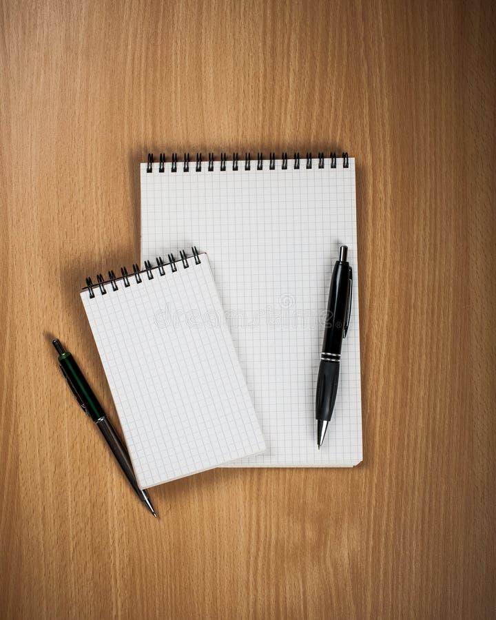 有笔的笔记本在木背景 免版税库存照片