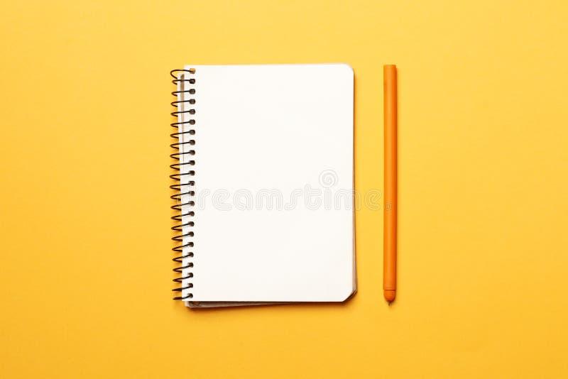 有笔的笔记本在黄色背景 图库摄影