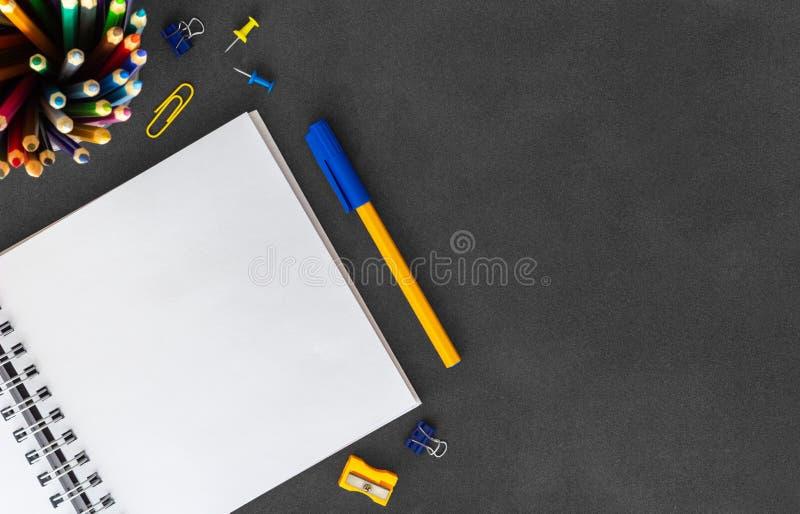 有笔的,切削刀刀子,橡皮擦,纸丛,纸夹,在黑暗的背景的推挤别针白色空白的螺旋纸笔记本 库存图片