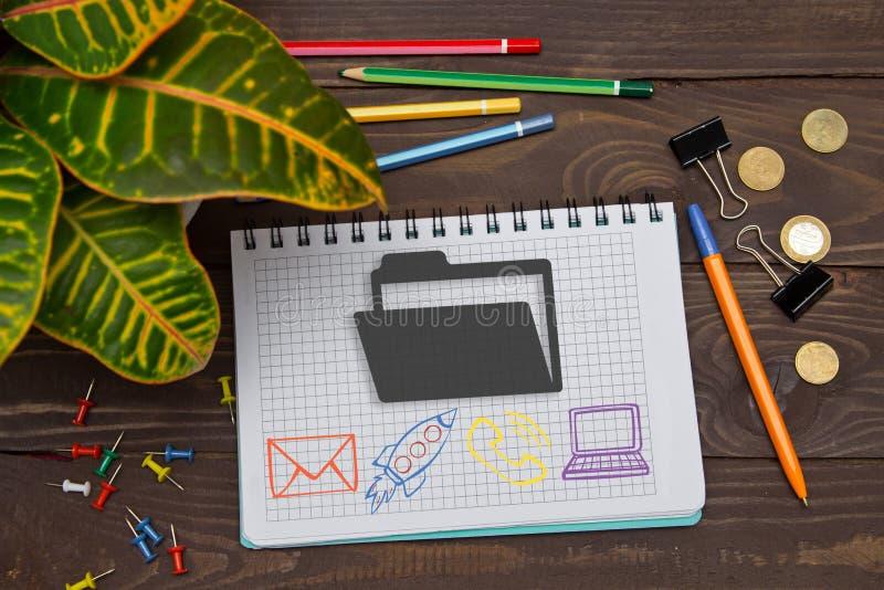 有笔记文件夹的笔记本在与工具的办公室桌上 库存照片