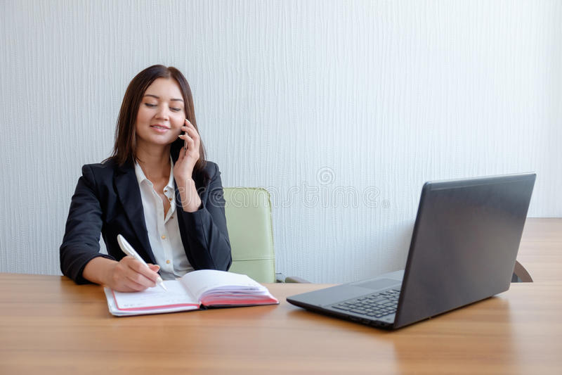 有笔记本、日历和手机的女商人在工作 免版税库存图片