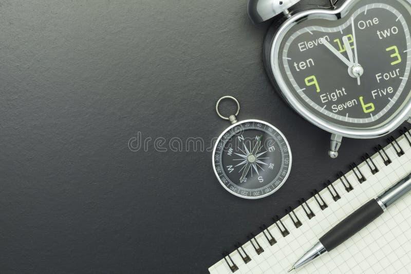 有笔记本、笔和闹钟的指南针在黑板backgrou 免版税库存图片