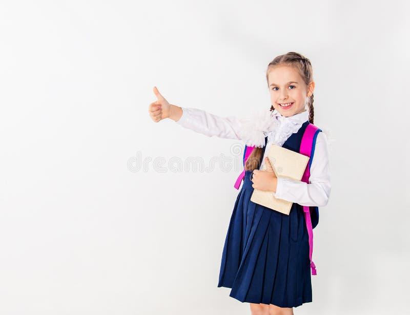 有笔记本和书的逗人喜爱的女小学生在白色背景 库存图片