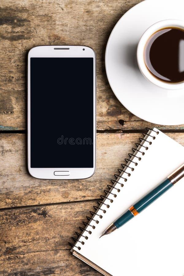 有笔记本和杯子的巧妙的电话浓咖啡 免版税库存照片