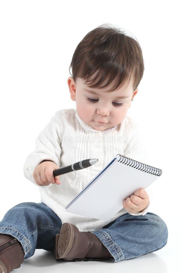 有笔记本和笔的婴孩 免版税库存图片