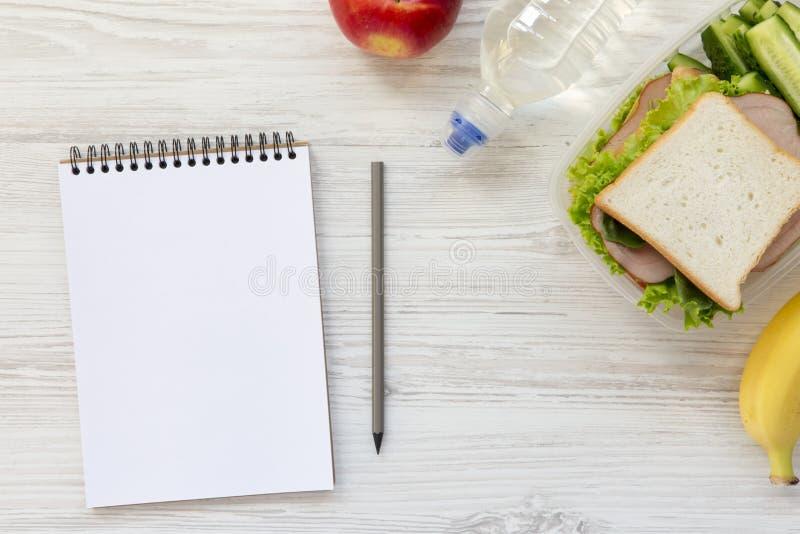 有笔记本和铅笔的健康学校午餐箱子在白色woode 免版税库存图片