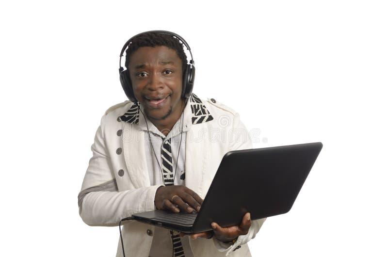 有笔记本和头电话的非洲DJ 库存照片