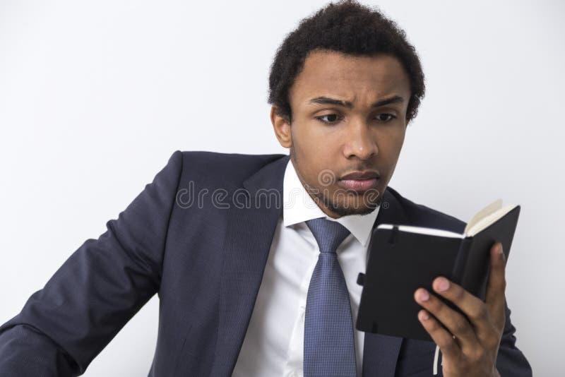有笔记本的严肃的非裔美国人的人 免版税库存照片