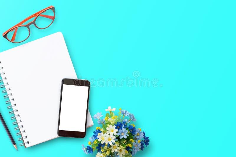 有笔记本的办公桌,智能手机,红色玻璃,铅笔,在蓝色桌背景的鲜花 库存照片