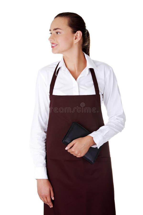 有笔记本的可爱的新女服务员在手中 免版税库存照片