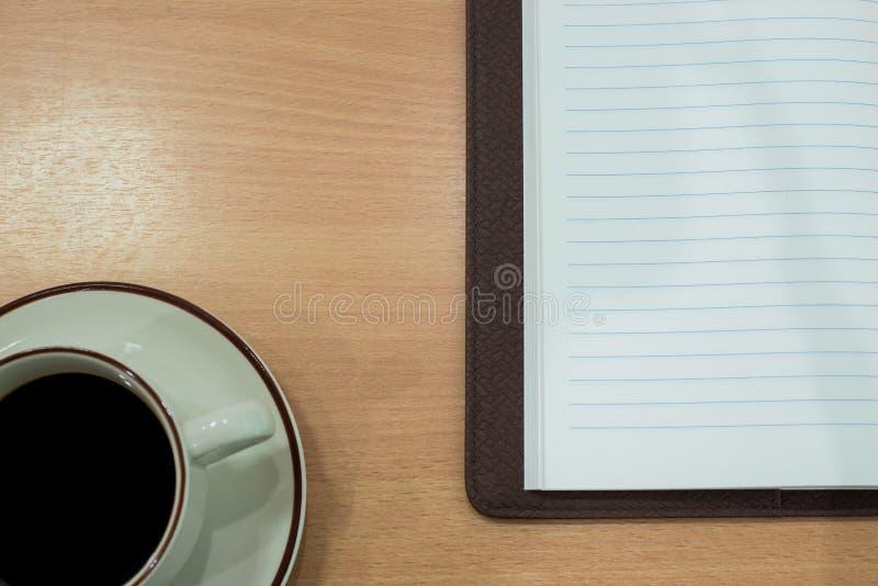 有笔记本的咖啡杯在木桌 为mockupe准备 免版税库存照片