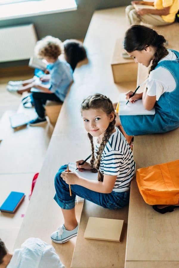 有笔记本的女小学生学习在论坛的大角度观点的在学校走廊,当她同学坐时 免版税库存图片